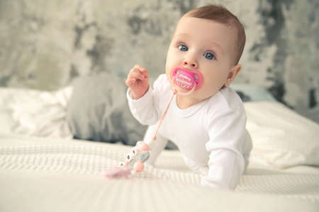 A baby with a pink pacifier in her mouth crawls on the bed.