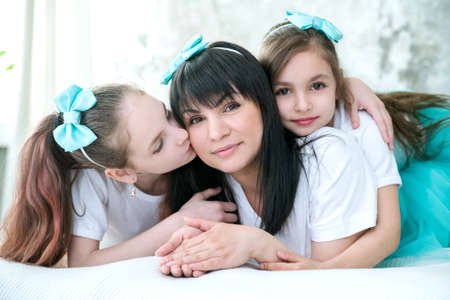 Daughters hug and kiss their beloved mother.