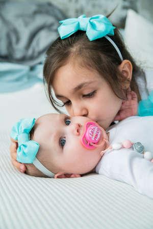 Girl kisses her newborn sister.