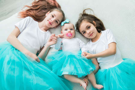 Two older sisters in beautiful ballet skirts hold their newborn sister by the arms.