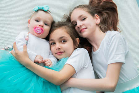 Three little sisters are hugging.