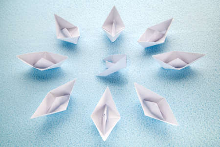 A sinking paper boat is surrounded by surviving boats awaiting help.