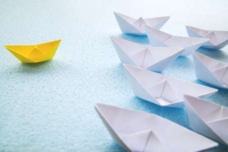 One yellow paper boat against dozens of large white ones. 写真素材