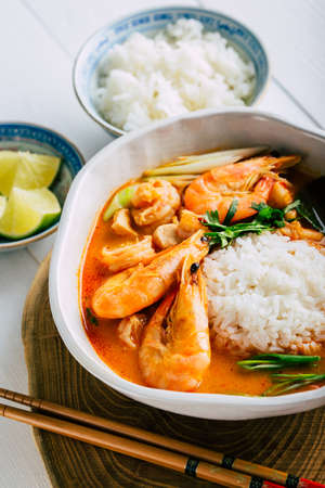 Tasty Tom Yam with shrimp and rice, spicy Thai soup, close-up