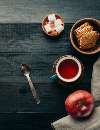 Tea and cookies on a black wooden table, copy space