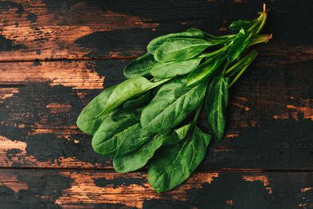 Bunch of fresh spinach on a dark wooden background