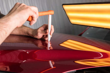 The technician removes dents on the car using the method without painting. PDR. Car body repair.