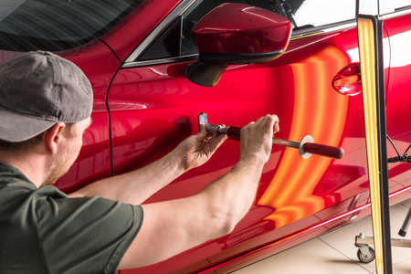 Repair of car dents. PDR technology. The master removes damage to the body.