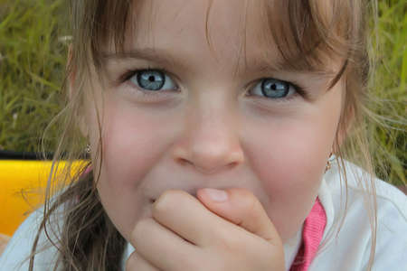 A cute EuropeanCaucasian little girl with big with blue expressive eyes looking directly into the camera
