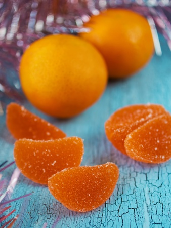 Tangerines and marmalade candies on olden blue wood photo