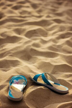 Slippers in sand, without people photo