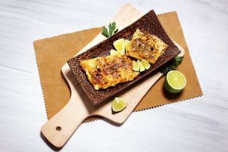 mango fish: Fried white fish, served with lime, on a rectangular dish made of mango wood
