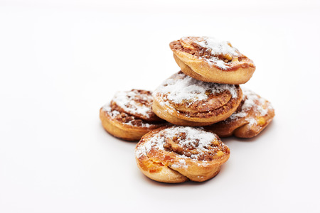Buns with cinnamon on white background. Sweet rolls with sugar powder.
