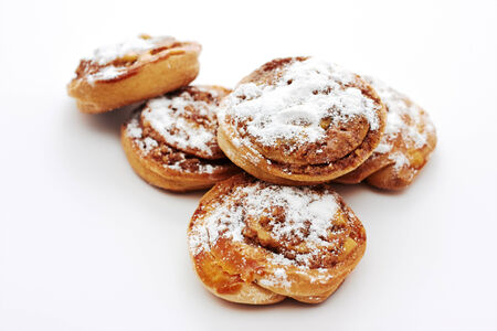 Buns with cinnamon on white background. Sweet rolls with sugar powder. photo