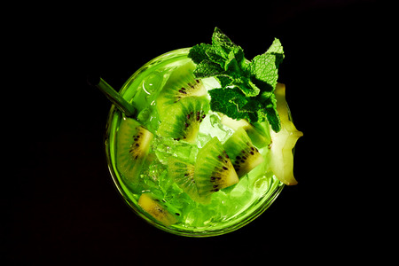 Green refreshing cocktail like mojito on dark background. Top view. With kiwi slices, mint and carambola. photo