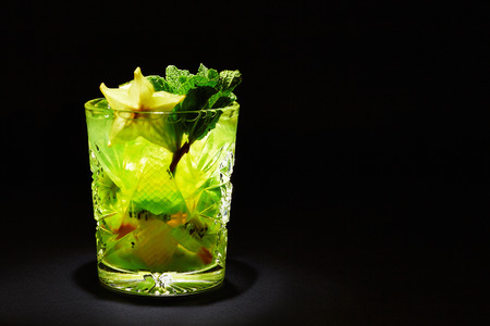 Green cocktail like mojito on dark background. With kiwi slices, mint and carambola. Space for your text. photo