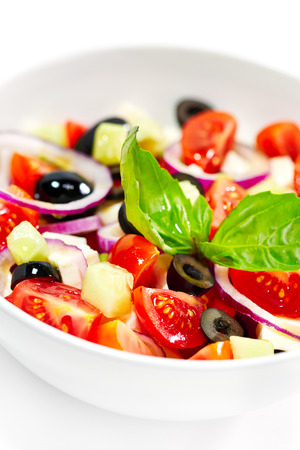 greek chef: Tasty greek salad with bright vegetables, garnished with basil.  Stock Photo