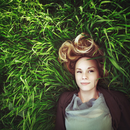 Beautiful young meditative woman in the grass. Summer, freedom concept. Blonde hair.Small amount of grain added for best final impression.