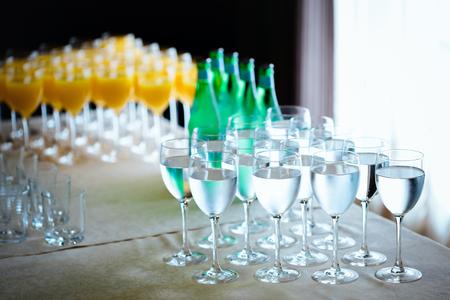 acqua di seltz: Catering bevande. Acqua, acqua gassata, succo d'arancia. Rinfresco. Messa a fuoco selettiva con sfondo bokeh. Archivio Fotografico