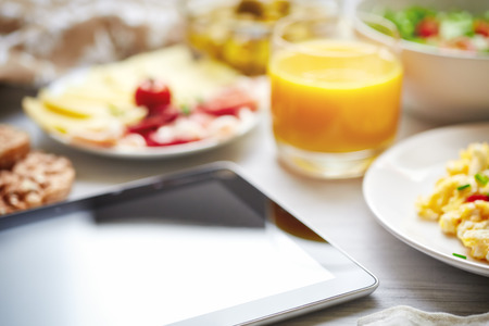 breakfast table: Fresh continental breakfast  Tablet, black screen, selective focus  Concept of business or holiday breakfast  Background, shallow depth of field