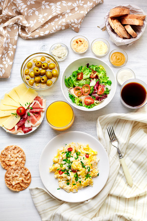omelette: Fresh breakfast table  Healthy food  Top view  Scrambled eggs, salad, cheese, prosciutto, coffee and juice  Concept of business or holiday breakfast