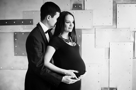 Young elegance pregnant family. Beautiful stylish couple. Black and white. photo