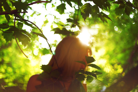 new age: Abstract background with woman silhouette behind leaves. Sunlight. Ecology, new age, peace concept.