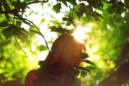 new age: Resumen de fondo con silueta de mujer detr�s de las hojas. La luz del sol. Ecolog�a, nueva edad, el concepto de la paz.
