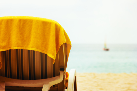 Tropical beach with beach chair and yellow towel. Holiday. photo
