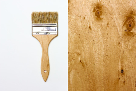 Renovation brush with white paper and wooden texture. Space for your text. photo