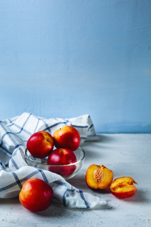 Five ripe nectarines on blue background with checked kitchen towel. Vertical composition. Selective focus. Stock Photo