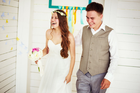 Happy young wedding couple, laughing and dancing. Selective focus on groom.
