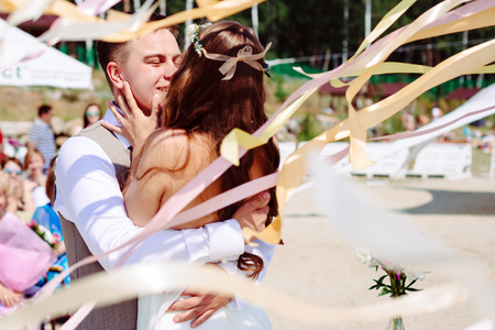 Wedding couple dancing and kissing in flying ribbons. Selective focus on groom.