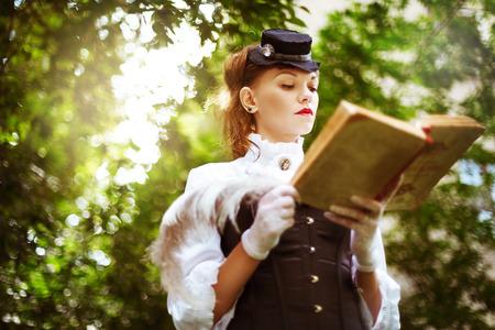 Vintage portrait of beautiful woman reading book photo