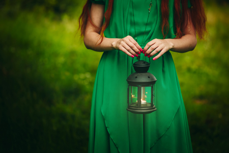 Woman with long red hair holding lantern with burning candle in forest. Concept of fairy-tale, mystery, fantasy. Standard-Bild