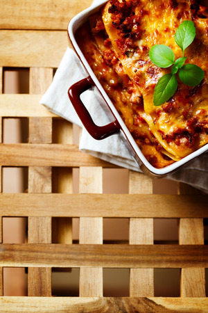 Hot tasty Lasagna plate served with fresh basil leaf.