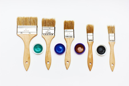 Set of five new brushes different size with color paint tests on white background photo