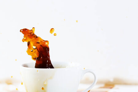 Cup of spilling coffee creating beautiful splash with stains on white. Coffee break, breakfast concept. photo