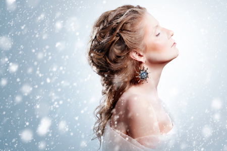 Winter beauty woman portrait with snowfall. Beautiful glamour model girl with Christmas fashion makeup and hairstyle showing trendy exclusive jewelry. Snow queen. Marie Antoinette style. Zdjęcie Seryjne