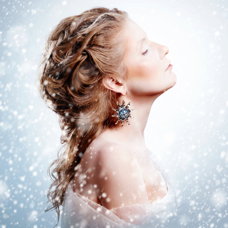 Creative woman portrait in vintage style. Beautiful glamour model girl standing under snowfall with closed eyes. Christmas fashion makeup and hairstyle. Snow queen. Marie Antoinette style. Image toned in warm instagram colors. Standard-Bild