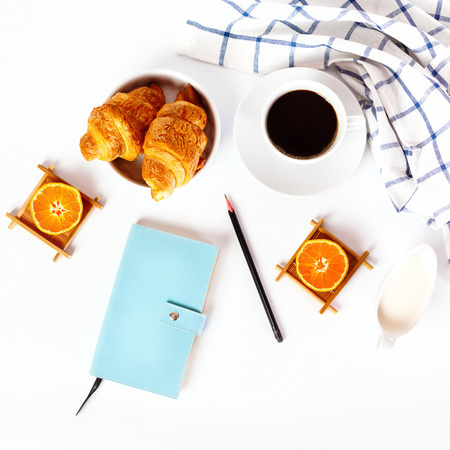 Breakfast concept. Coffee and oranges and fresh baked tasty croissant on white background. Personal diary with pencil for successful day.