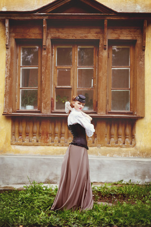 Beautiful redhair woman in vintage clothes standing near old ancient house with wooden window. Toned in warm vintage colors. Stock Photo