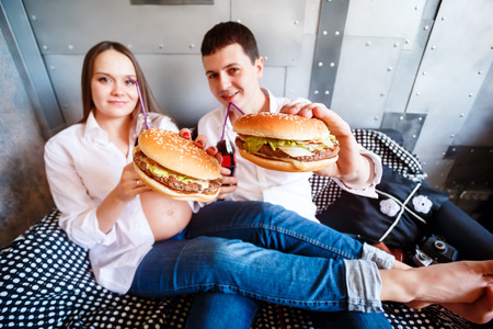 pregnant jeans: Young happy pregnant family resting and eating fast food. Fresh cheeseburger and soda water. Wide angle shot, selective focus on burgers. Man and woman dressed in jeans and white shirts.