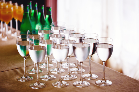 glass  reflection: High glasses with water served on cafe table. Row of shiny glasses with reflections in day light. Stock Photo
