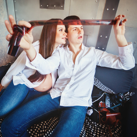 pregnant jeans: Young happy pregnant family have fun and looking film tape with their photos. Man and woman dressed in jeans and white shirts.  Stock Photo