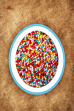 sprinkling: Colorful easter background with different sweet sprinkling on craft paper background. Holiday treat.