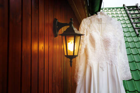 White wedding dress close up ready for bride. Roof background, romantic warm lantern. Selective focus on dress. photo