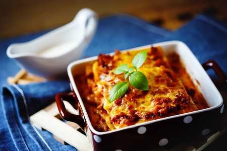 Italian Food. Hot tasty Lasagna plate served with fresh basil leaf and white sauce. Stock Photo
