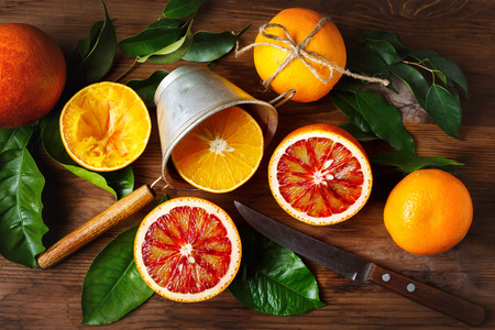 still life: Still life with orange fruit and green leaves on wooden table. Top view. Stock Photo