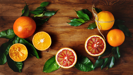 Orange fruit among green leaves on wooden table. Top view.